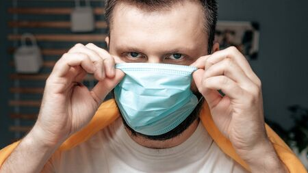 Guy puts on surgical mask. Attractive man puts on face mask and looks at camera. Cold, flu, virus, tonsillitis, acute respiratory disease, quarantine, epidemic concept. Close-up