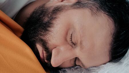 Guy has fever. Young Caucasian man lies on bed of his shakes. Colds, flu, cold sweat, virus, acute respiratory illness, chills concept. Close-up