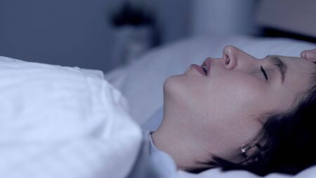 Girl snores. Stuffy nose, apnea, curvature of nasal septum, fatigue concept. Young attractive woman sleeps on her back in bed with open mouth. Close-up