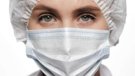 Close-up of concentrated woman doctor in surgical mask is looking at camera. Operation, medical practitioner, surgery, transplant, healthcare, medicine, COVID-19 concept