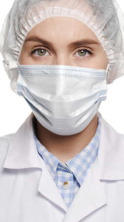 Close-up of concentrated woman doctor in surgical mask is looking at camera. Operation, medical practitioner, surgery, transplant, healthcare, medicine, COVID-19 concept. Close-up 写真素材