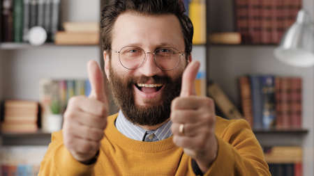 Man thumb up. Positive laughing bearded man in glasses in office or apartment room looking at camera and shows his two hands thumb up. Close-up 写真素材