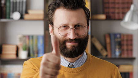 Man thumb up. Positive smiling bearded man in glasses in office or apartment room looking at camera and shows his thumb up. Close-up