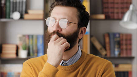 Man thinking, brainstorm, good idea concept. Concentrated bearded man in glasses in office or room in apartment with pensive face looking around thinks and brainstorm. Close-up