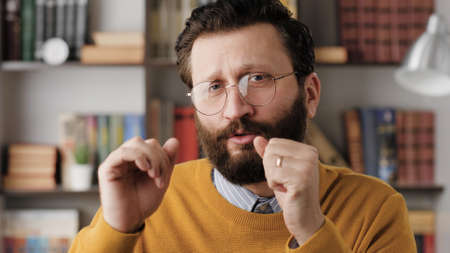 Man is dancing. Positive bearded man office worker in glasses in office or apartment room looking at camera and dances. Close-up