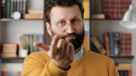 Man beckons with his finger. Serious frowning bearded man with glasses in office or apartment room looking at camera and points his fingers, gesturing to him. Close-up