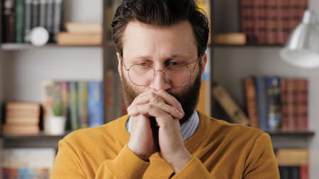 Man is praying. Upset bearded man with glasses in office or apartment room brings his hands to his face and say prayer. Close-up 写真素材