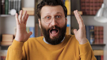 Man is scared, terrified. Frightened bearded man in glasses in office or room in apartment with suddenly throws his hands up and looking at camera, he is very scared and just terrified. Close-up
