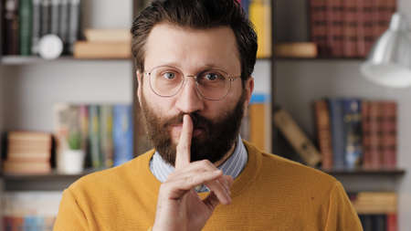 Shh, man secret finger. Suspicious bearded man in glasses in office or apartment room looking at camera and brings his index finger to his mouth lips and she say shhh. Close-up