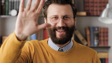 Man waving HELLO. Positive smiling laughing man in office or apartment room looking at camera and waving right hand showing and says greeting HI. Close-up