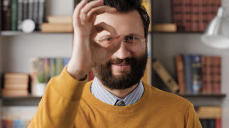 Man shows OK. Positive smiling bearded man in glasses in office or apartment room looks at camera and shows OK gesture with his fingers. Close-up 写真素材