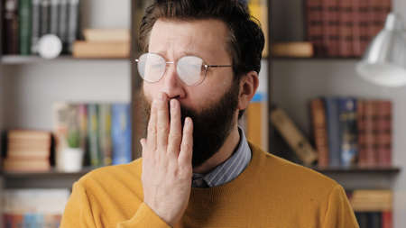 Man yawns. Tired sad bearded man in glasses in office or apartment room yawns, he covers his mouth with his hand. Close up