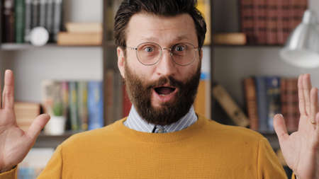 Man is surprised, shocked. Smiling bearded man in glasses in office or apartment room looking at camera and waves his hands emotionally expressing his incredible surprise. Close up