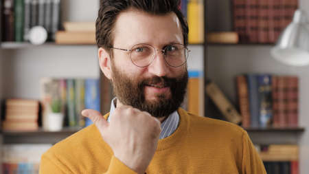 YES emotion gesture. Excited joyful bearded man with glasses in office or apartment room looking at camera and emotionally clenches his hand into fist and shows his satisfaction and possibly victory 写真素材