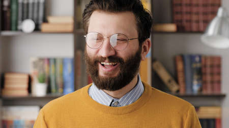 Man smiling, laughs. Positive joyful bearded man in glasses in office or apartment room looking at camera and smiles and laughs shyly. Close-up
