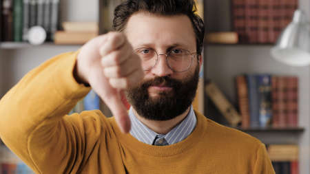 Man thumbs down. Serious displeased bearded man with glasses in office or apartment room looking at camera and shows his hand with thumb down. Close-up 写真素材