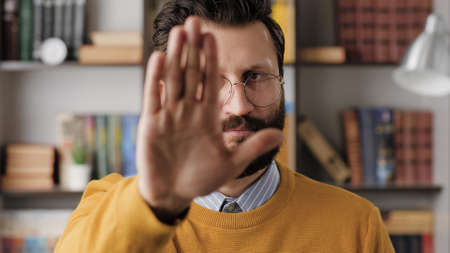 Man show STOP, NO. Serious displeased bearded man in glasses in office or apartment looking at camera and shows his palm STOP. Close-up
