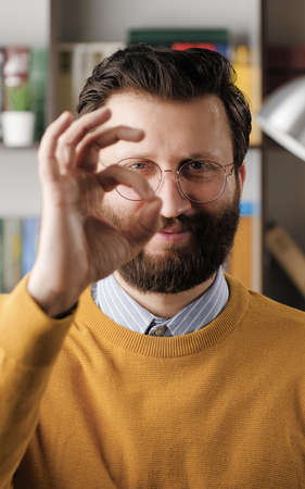 Man shows OK. Positive smiling bearded man in glasses in office looks at camera and shows OK gesture with his fingers. Close-up