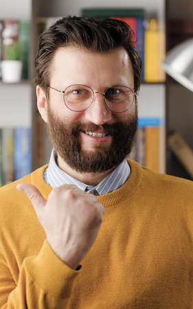 YES emotion gesture. Excited joyful bearded man with glasses looking at camera and emotionally clenches his hand into fist and shows his satisfaction and possibly victory. Close-up
