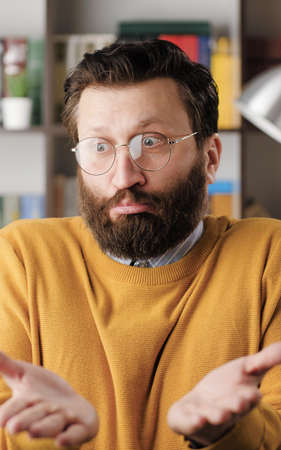 Shrug, i dont know. Perplexed bearded man in glasses in office or apartment room looking at camera and emotionally squeezes his shoulders and spreads his hands to show his ignorance. Close up