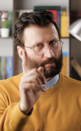 Man threatens with his finger. Serious frowning bearded man in glasses in office or apartment room looking at camera and points menacingly with his index finger. Close up