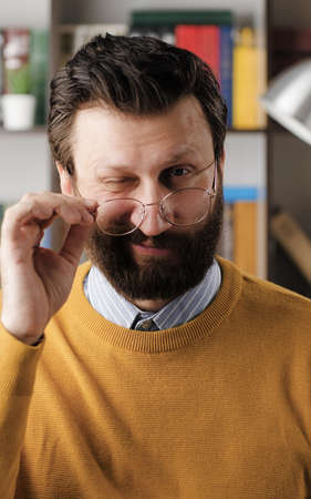 Man winks. Positive smiling bearded man with glasses in office or apartment room looking at camera and slowly lowers his glasses and winks. Close up 写真素材