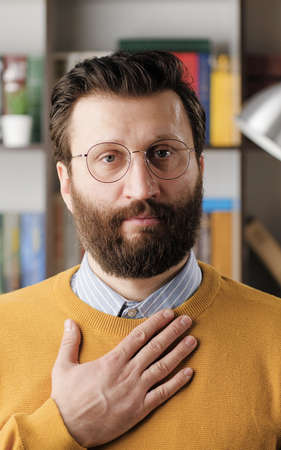 Respect bow. Bearded man with glasses in office or apartment room looking at camera and puts his hand on his chest and bows, expressing respect or greeting. Close-up