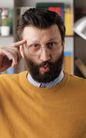 Stupid. Irritated bearded man in glasses in office or apartment room looks at camera and twirls his finger at his temple. Close-up