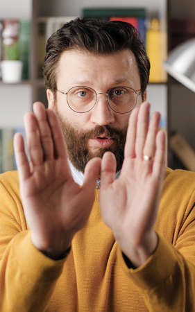 Disagreement, stop, NO says. Frightened worried bearded man in glasses looks at camera and starts waving his arms nervously, shouting no-no-no. Close-up
