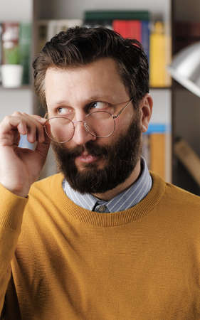 Skepticism, sarcasm emotion. Bearded man in glasses in office or apartment room expressing his skeptical attitude and discontent with his look. Close up