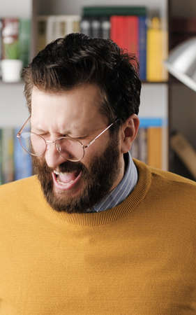 Man scream. Bearded man in glasses in office or apartment room close his eyes and screams. Close-up