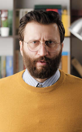 Angry man, rage. Angry annoyed bearded man in glasses in office or apartment room looking at camera. Close-up