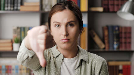 Woman thumb down. Frowning serious woman in office or apartment room looking at camera raises her hand and shows her thumb down. Medium shot