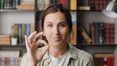 Woman shows OK. Positive smiling woman in office or apartment room looks at camera and shows OK gesture with her fingers. Medium shot