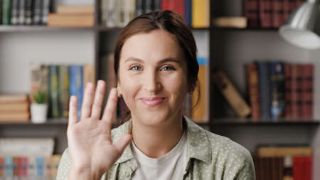 Woman waving HELLO. Positive smiling woman in office or apartment room looking at camera and waving right hand showing and says greeting HI. Medium shot