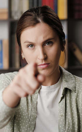 Woman points to you. Serious frowning woman looking at camera and points her finger in camera. Medium shot