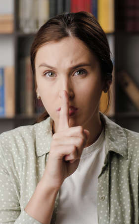Shh, woman secret finger. Suspicious woman in office or apartment interior looking at camera and brings her index finger to her mouth lips and she say shhh. Medium shot