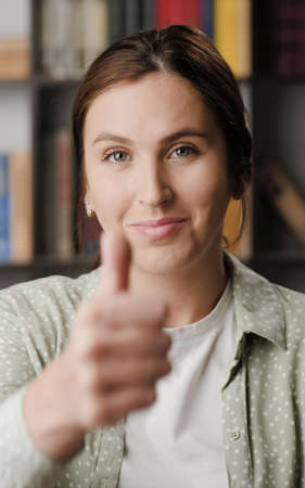 Woman thumb up. Positive smiling woman in office or apartment room looking at camera and shows her thumb up. Medium shot