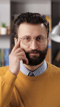 Just think gesture emotion. Vertical view of positive bearded man teacher or businessman with glasses looking at camera and tapping his finger on his temple, suggests thinking well Stock fotó
