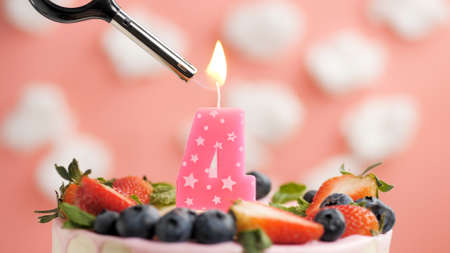 Birthday cake number 4, pink candle on beautiful cake with berries and lighter with fire against background of white clouds and pink sky. Close-up