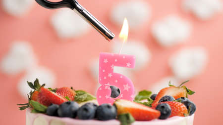 Birthday cake number 5, pink candle on beautiful cake with berries and lighter with fire against background of white clouds and pink sky. Close-up