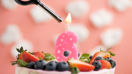 Birthday cake number 6, pink candle on beautiful cake with berries and lighter with fire against background of white clouds and pink sky. Close-up Imagens