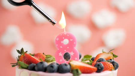 Birthday cake number 8, pink candle on beautiful cake with berries and lighter with fire against background of white clouds and pink sky. Close-up