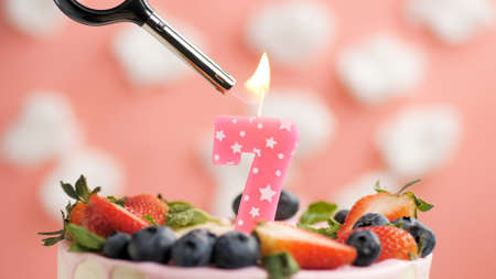 Birthday cake number 7, pink candle on beautiful cake with berries and lighter with fire against background of white clouds and pink sky. Close-up