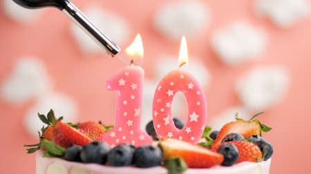 Birthday cake number 10, pink candle on beautiful cake with berries and lighter with fire against background of white clouds and pink sky. Close-up Imagens