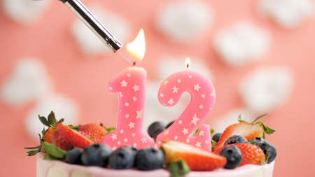 Birthday cake number 12, pink candle on beautiful cake with berries and lighter with fire against background of white clouds and pink sky. Close-up