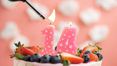 Birthday cake number 14, pink candle on beautiful cake with berries and lighter with fire against background of white clouds and pink sky. Close-up Imagens