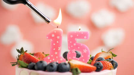 Birthday cake number 15, pink candle on beautiful cake with berries and lighter with fire against background of white clouds and pink sky. Close-up