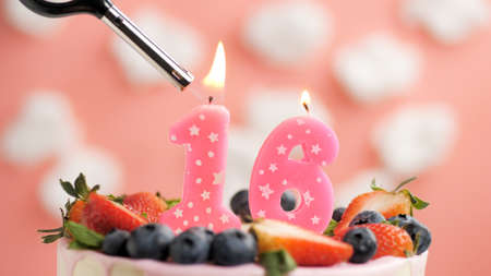 Birthday cake number 16, pink candle on beautiful cake with berries and lighter with fire against background of white clouds and pink sky. Close-up Imagens