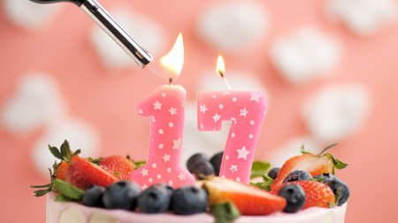 Birthday cake number 17, pink candle on beautiful cake with berries and lighter with fire against background of white clouds and pink sky. Close-up